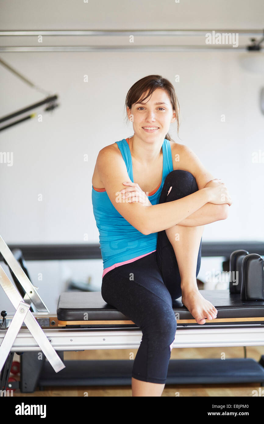 Portrait of young woman sitting on reformer in pilates gym - Stock Image