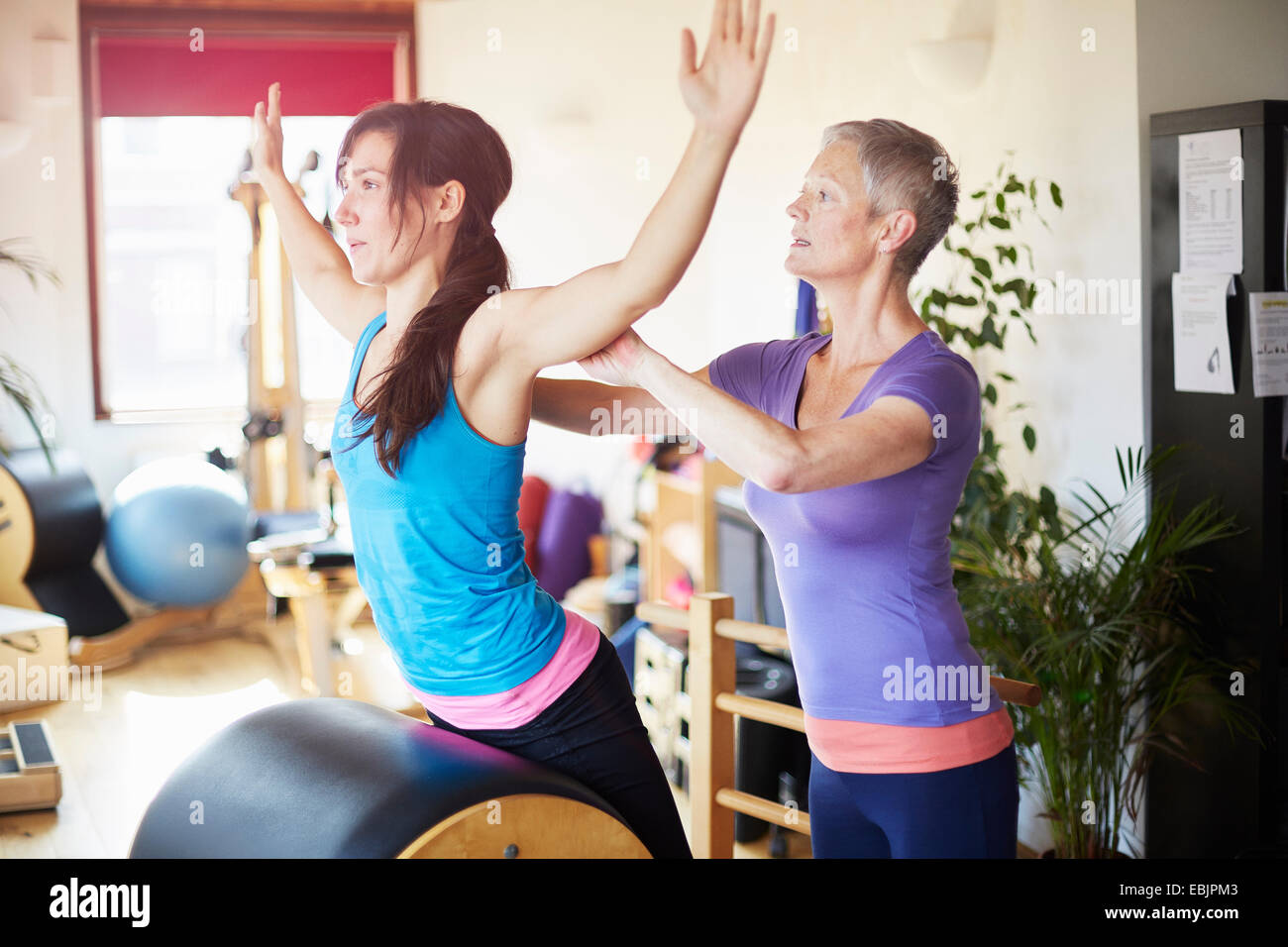 Female student leaning forward onto pilates barrel in pilates gym - Stock Image