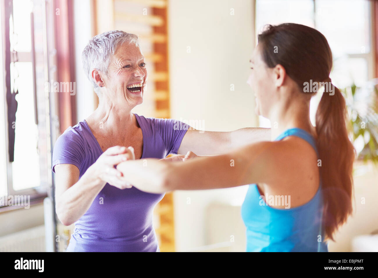 Young female student laughing with teacher in pilates gym - Stock Image