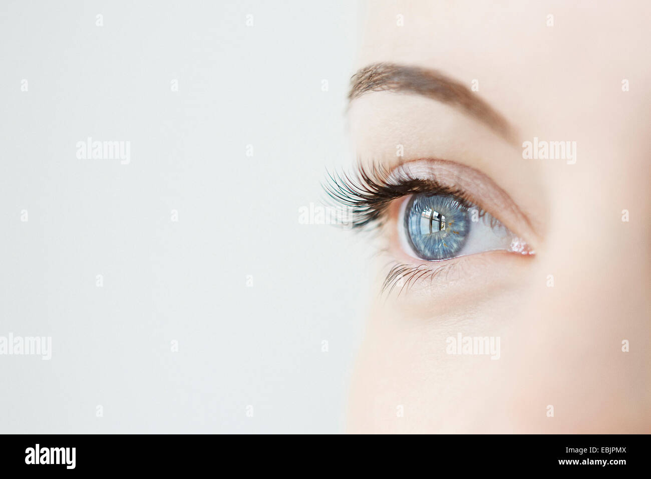 Studio close up of mid adult womans gazing blue eye - Stock Image