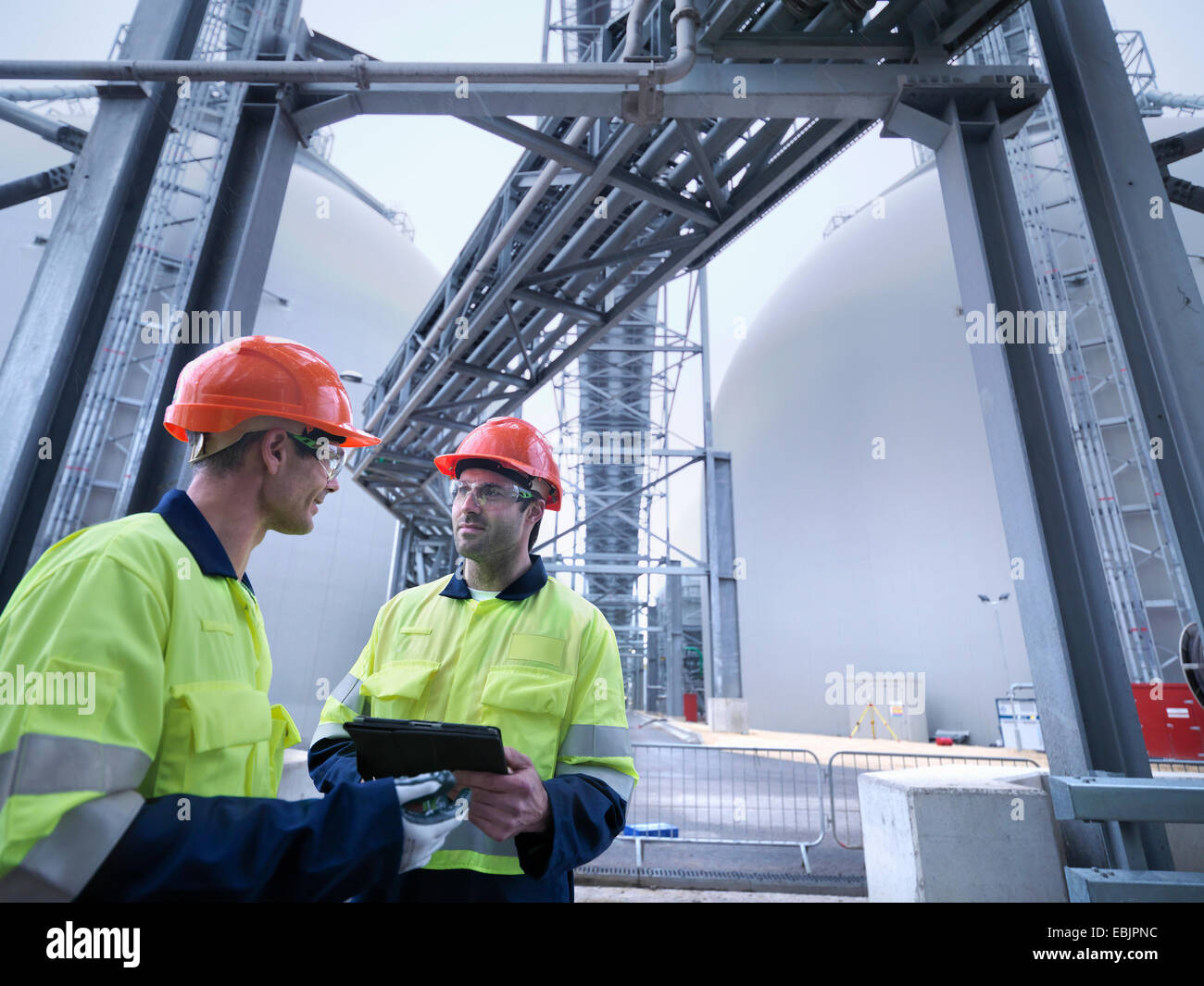 Workers using digital tablet at biomass facility - Stock Image