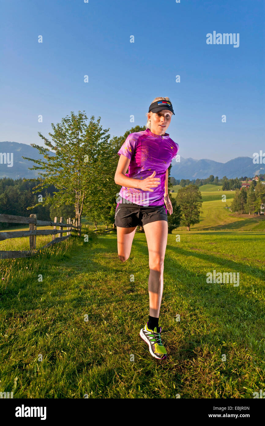 young woman trail running in a meadow and forest landscape, Austria, Styria, Dachstein Stock Photo