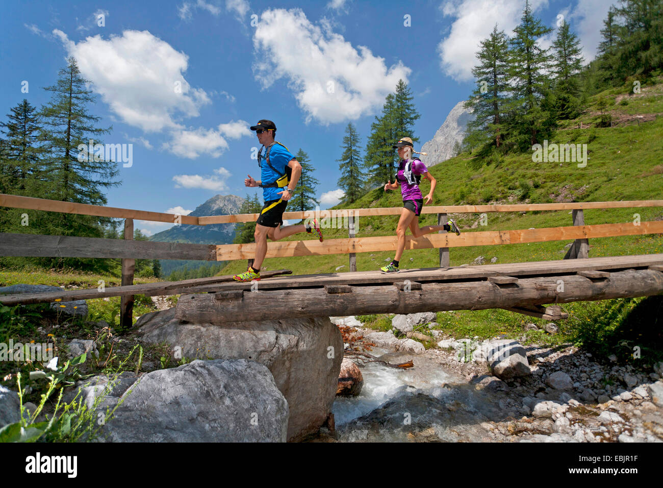 young couple running over a wooden bridge over a brook while trail running in the Dachstein Mountains, Austria, - Stock Image