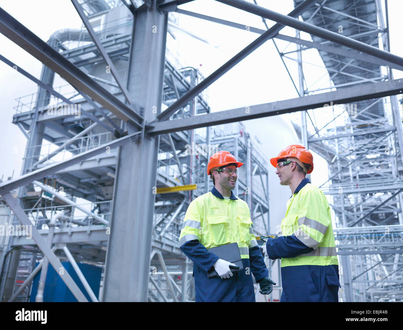 Workers in discussion in biomass facility - Stock Image