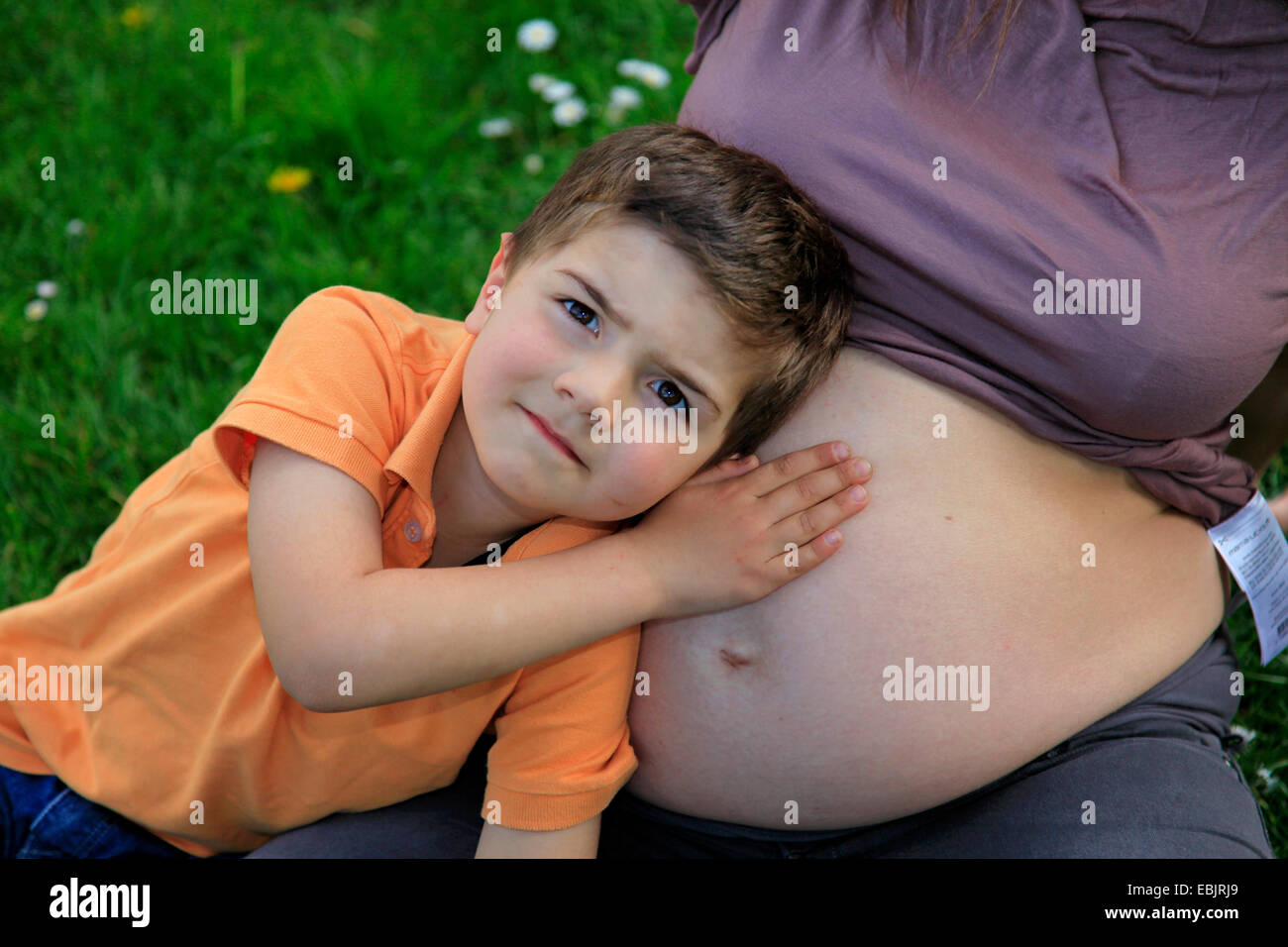 little boy leaning against the belly bump of his mother - Stock Image