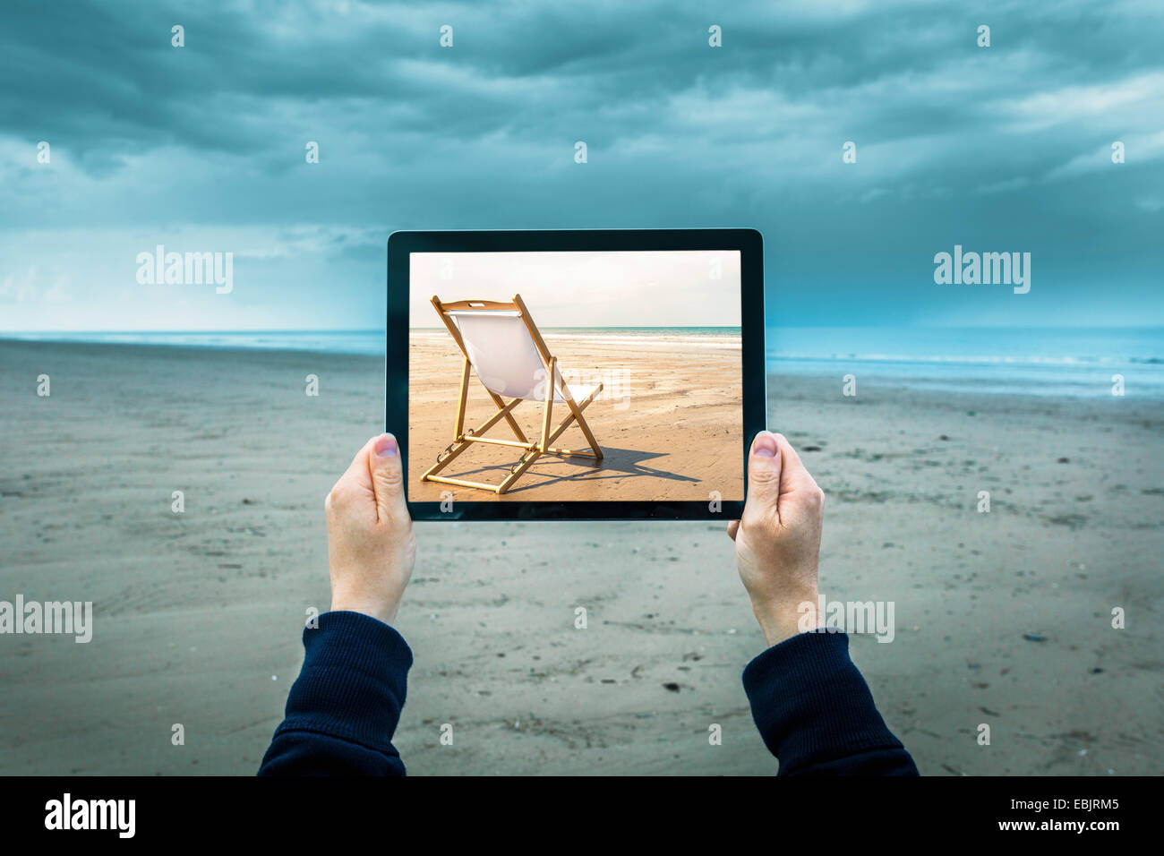 Mature woman on cloudy beach, holding digital tablet showing sunny beach scene, focus on hands and laptop - Stock Image