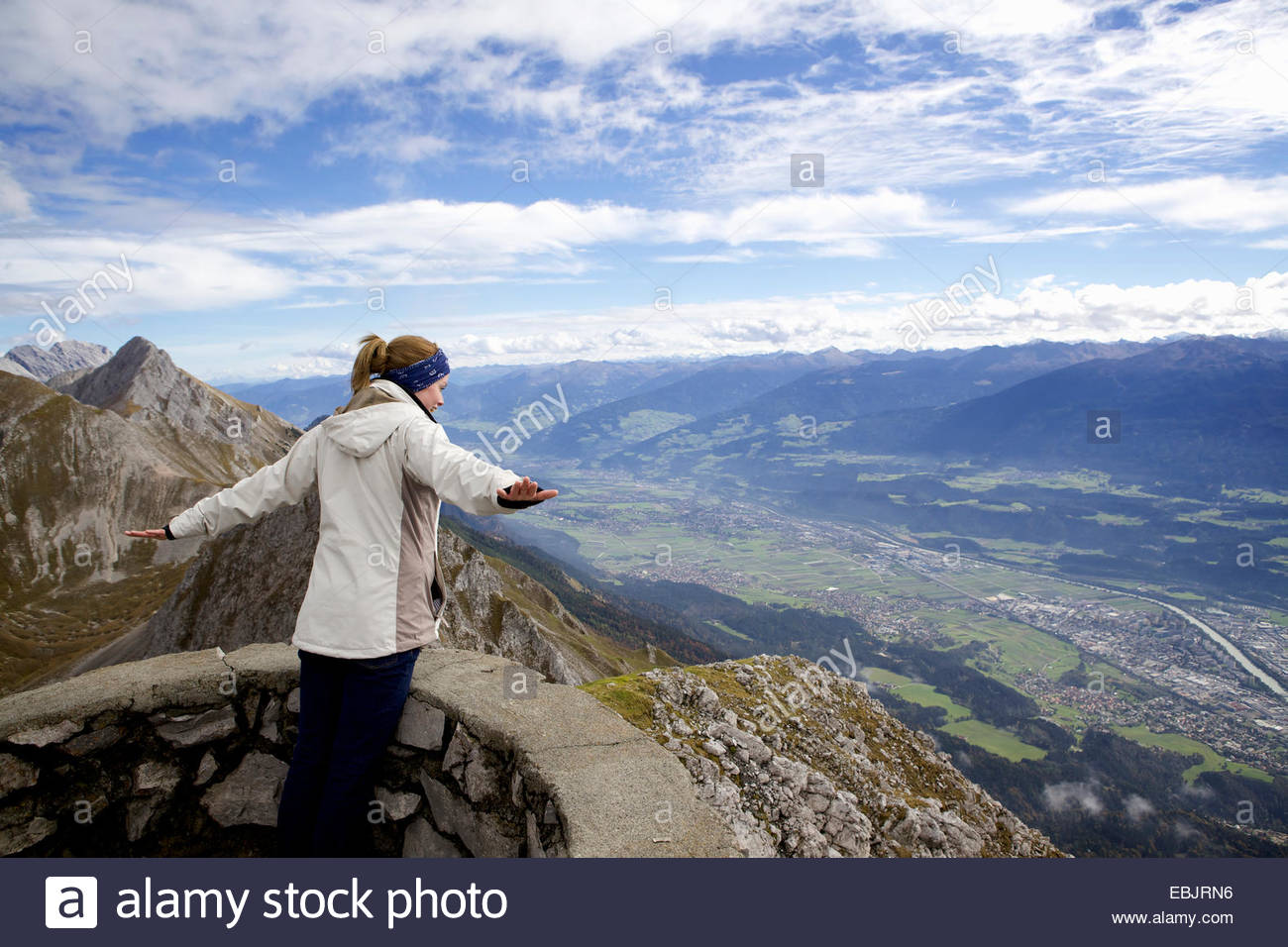 Young woman with arms open on top of mountain, Innsbruck Tyrol, Austria - Stock Image