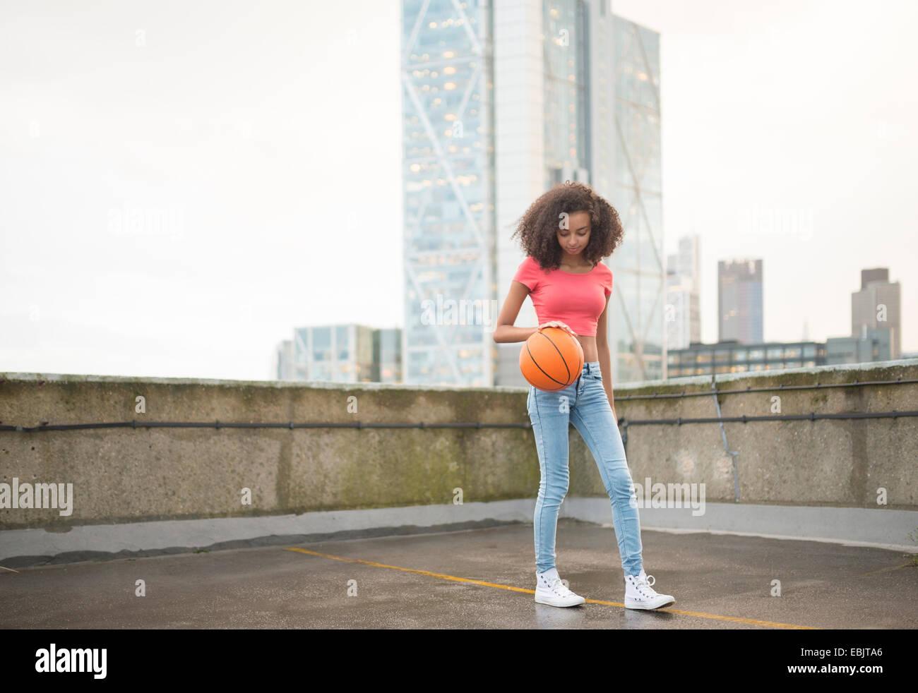 Young woman bouncing basketball - Stock Image