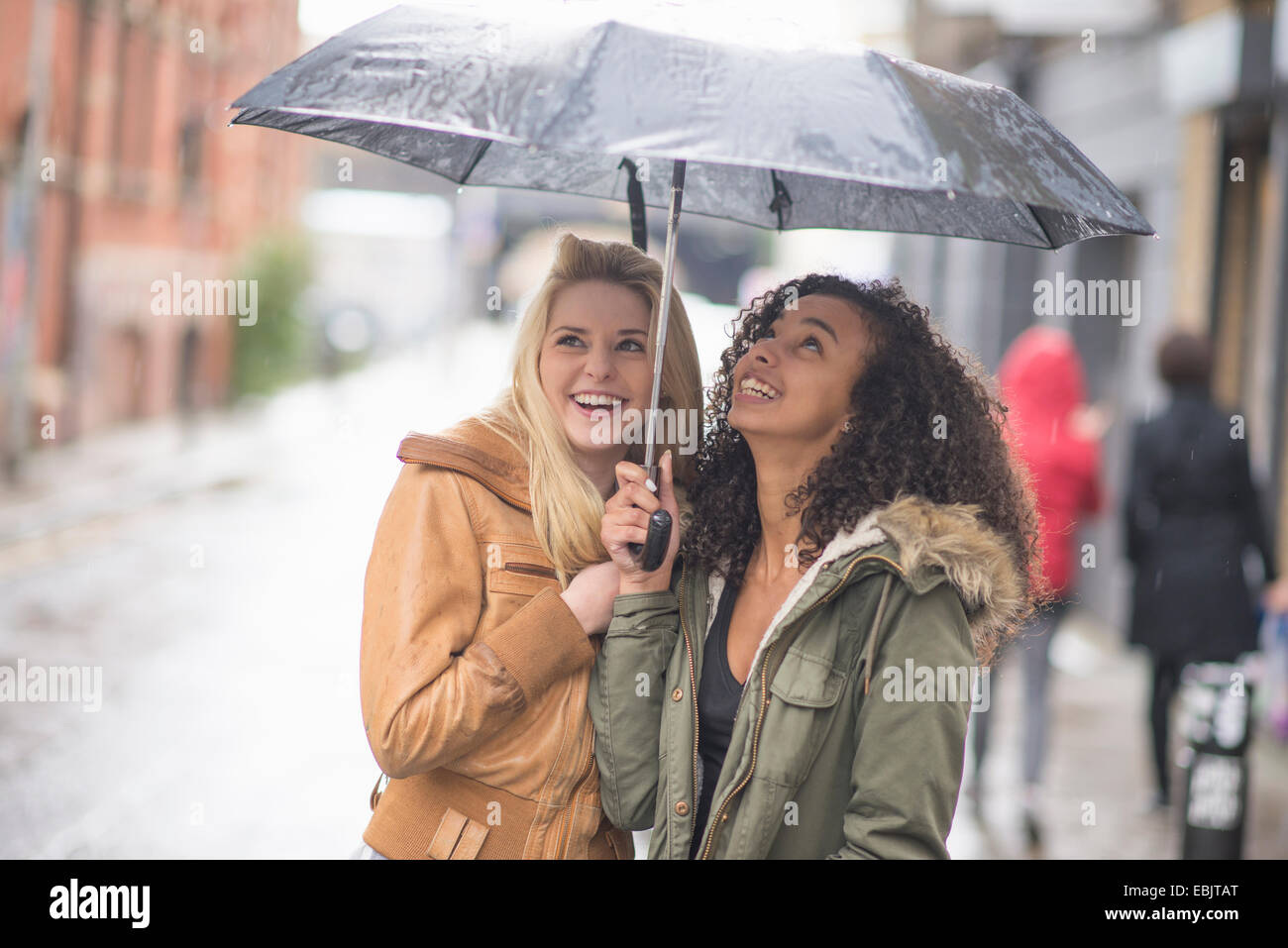 Young women sheltering under umbrella - Stock Image
