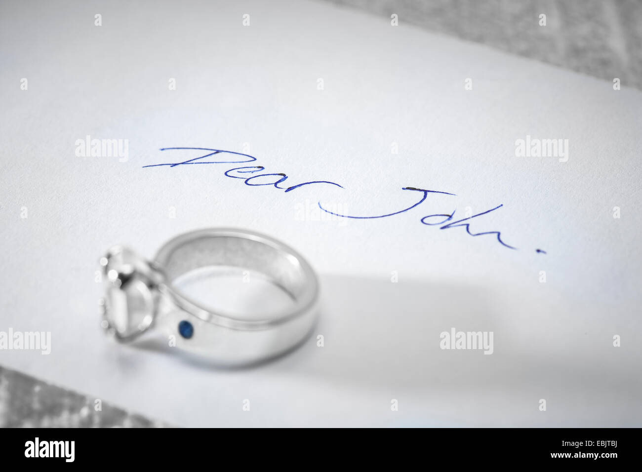 Returned engagement ring on a Dear John letter. - Stock Image