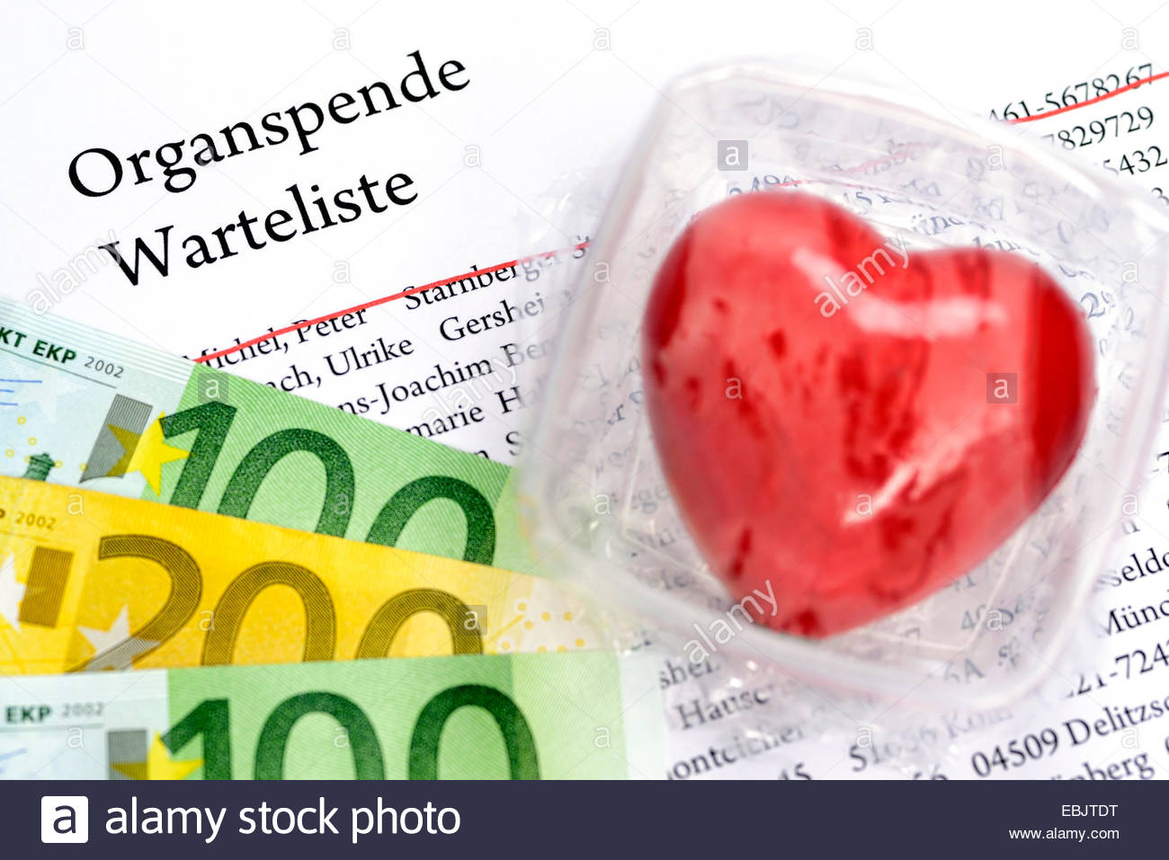 symbol picture 'organ donation cheat': heart in a food storage box, waiting list and Euro bills - Stock Image