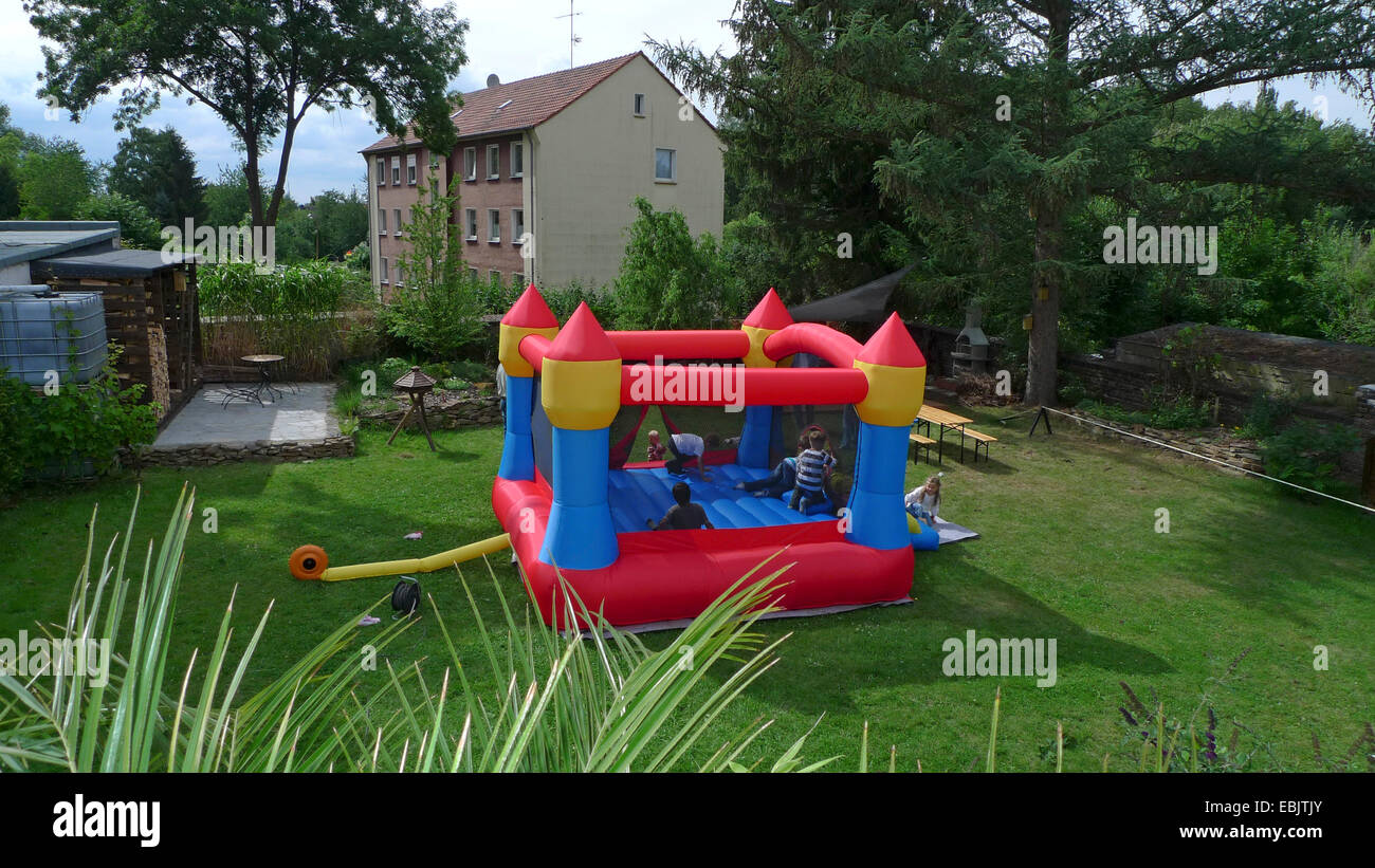 kids playing amused on an inflatable castle in a garden, Germany - Stock Image