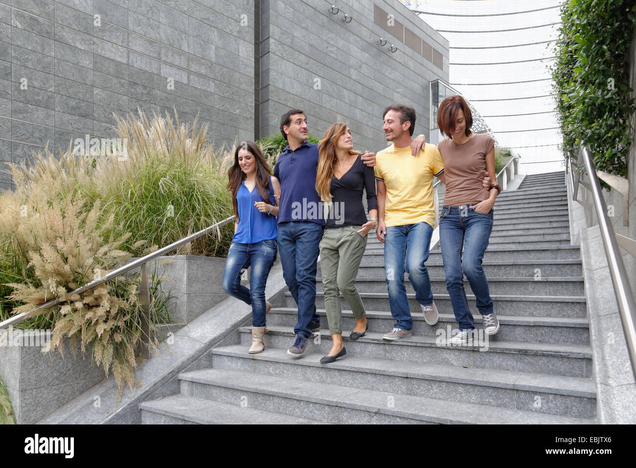 group of friends walking down steps together stock photo 76017374