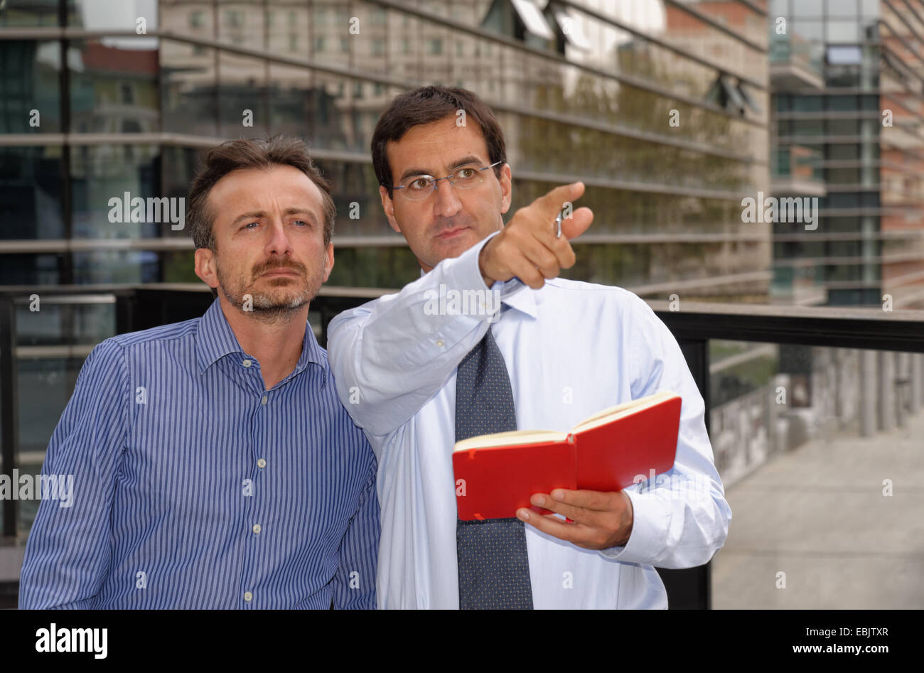Two men having discussion, pointing and looking ahead - Stock Image