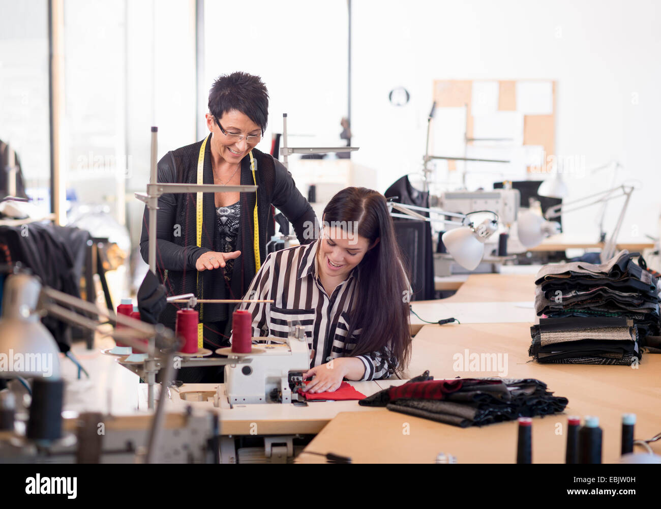 Two seamstresses at sewing machine in workshop - Stock Image