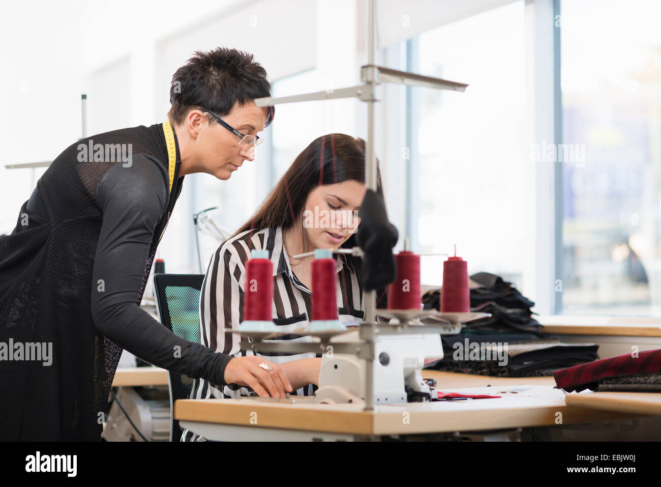 Two seamstresses looking down at sewing machine in workshop - Stock Image