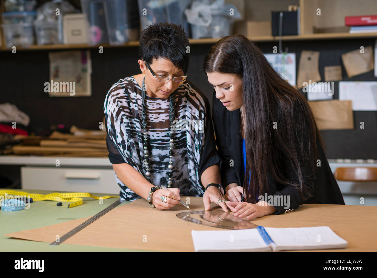 Two seamstresses using curved ruler on dressmakers pattern in workshop - Stock Image