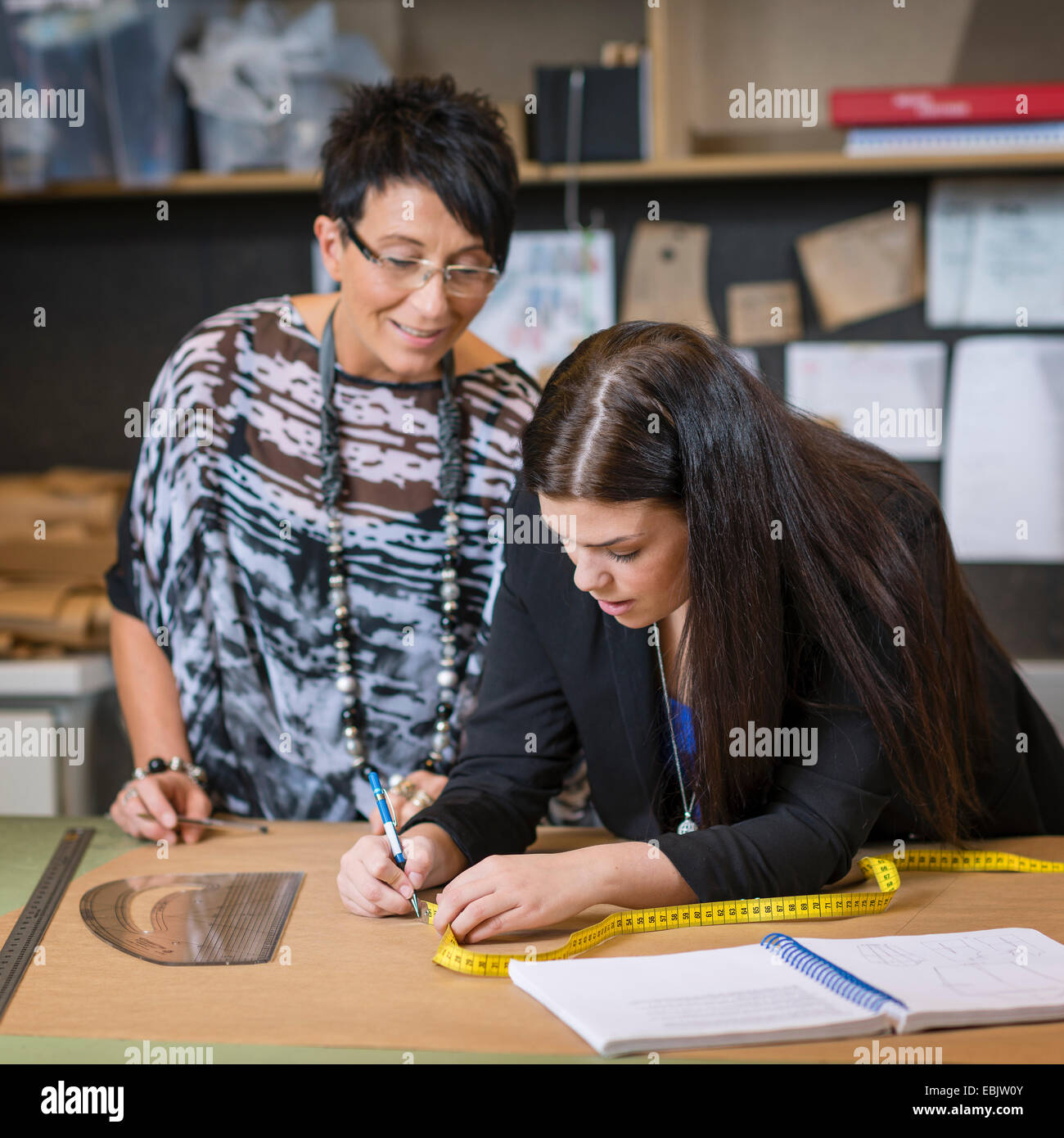 Two seamstresses making dressmakers pattern in workshop - Stock Image