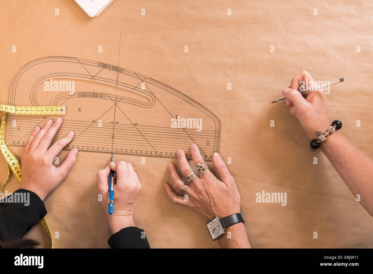 Overhead view of seamstresses hands drawing with curved ruler on dressmakers pattern in workshop - Stock Image