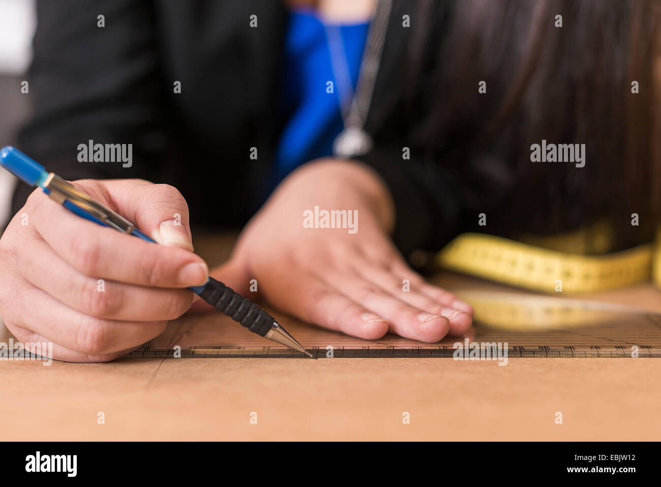 Close up of young seamstress drawing with ruler on dressmakers pattern in workshop - Stock Image