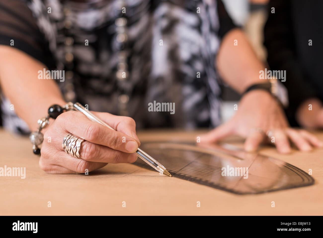 Close up of mature seamstress drawing with curved ruler on dressmakers pattern in workshop - Stock Image