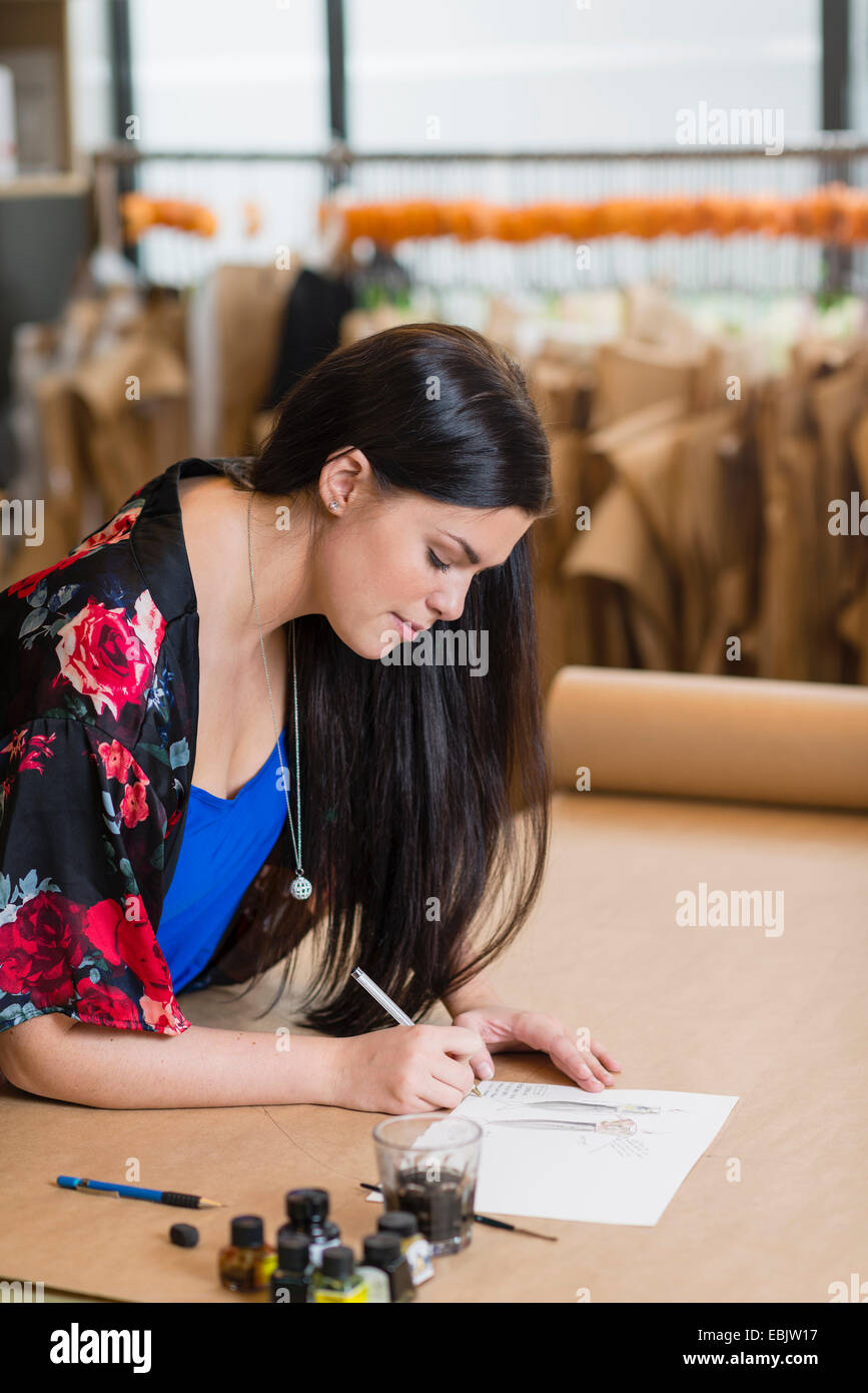 Young seamstress painting fashion design in workshop - Stock Image