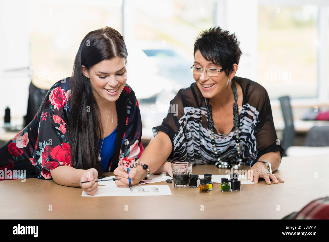 Two seamstresses painting fashion design on work table - Stock Image