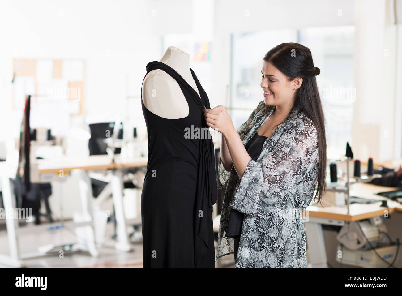 Young seamstress fitting dress on tailors dummy in workshop - Stock Image