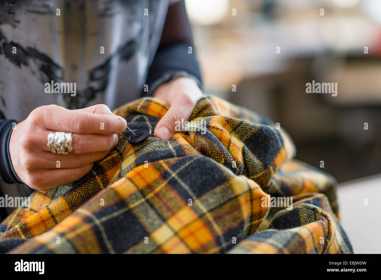 Close up seamstress hand sewing button onto tartan jacket in workshop - Stock Image