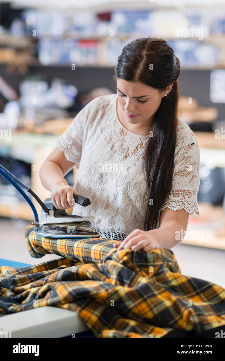 Young seamstress ironing tartan jacket in workshop - Stock Image