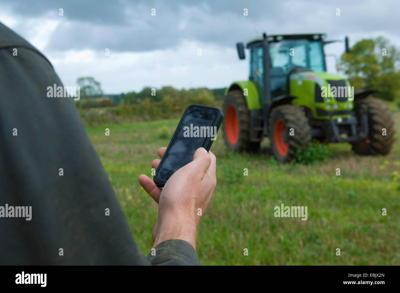 Male farmers hand holding up smartphone in field - Stock Image