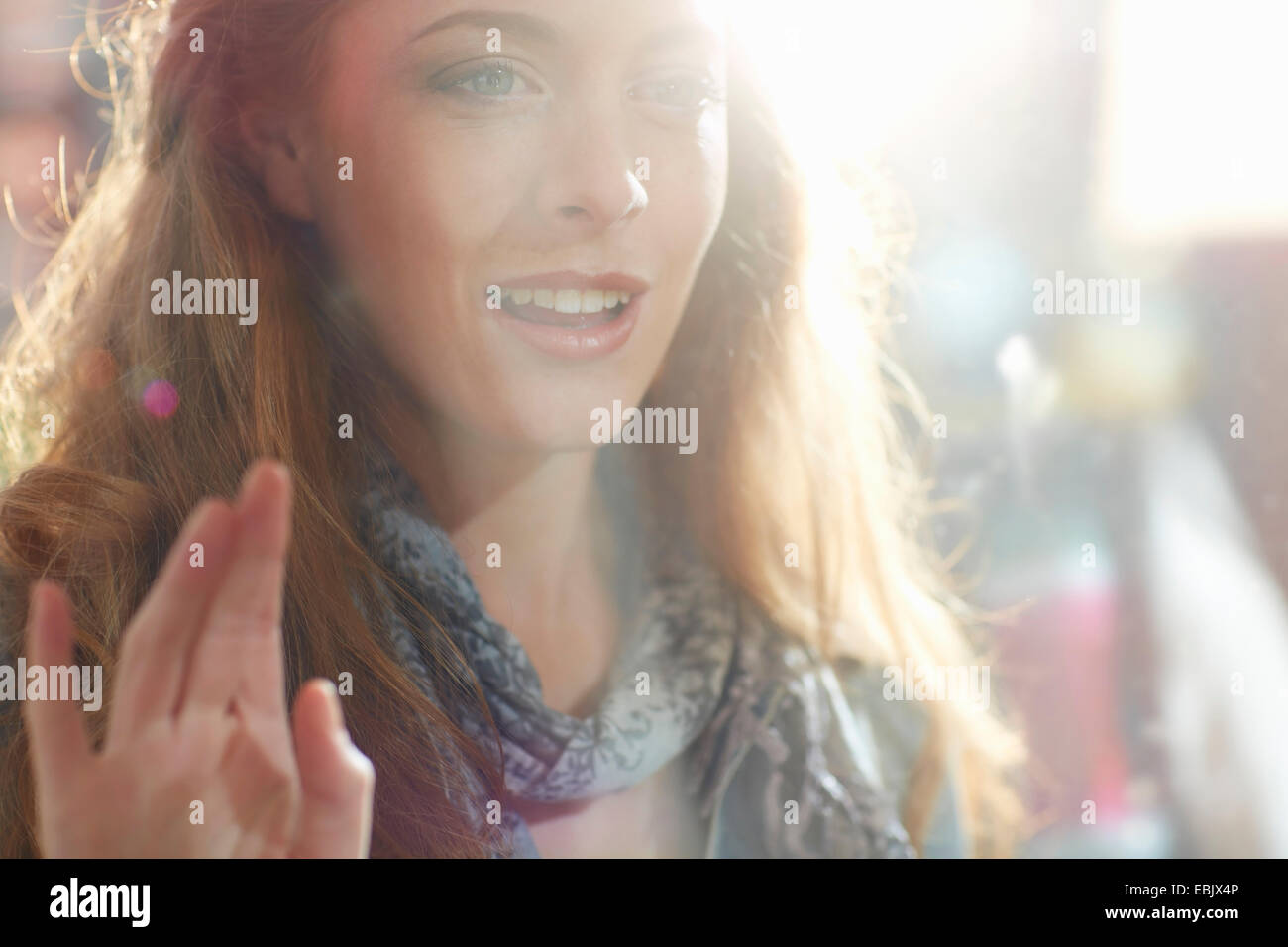 Young woman looking in shop window - Stock Image