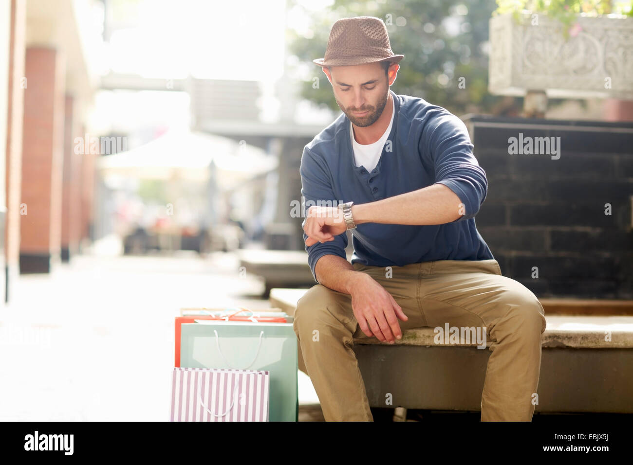 Mid adult man sitting on seat, looking at watch, shopping bags beside him - Stock Image