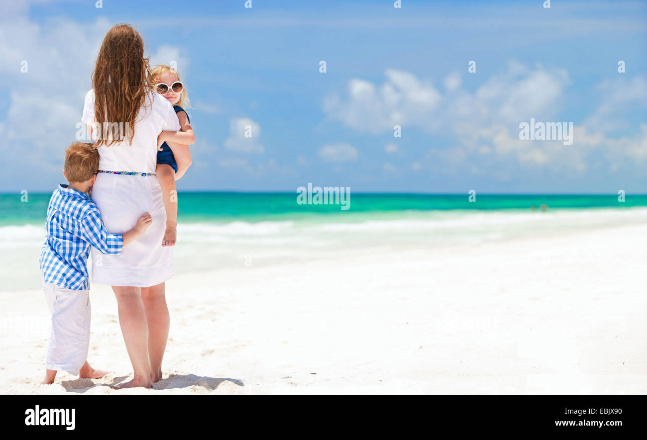 mother and two little children standing on sandy beach, Mexico Stock Photo