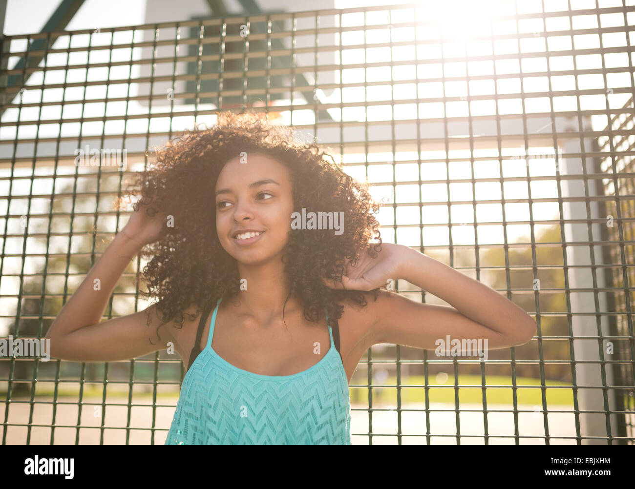 Portrait of young female basketball player with hands in hair - Stock Image