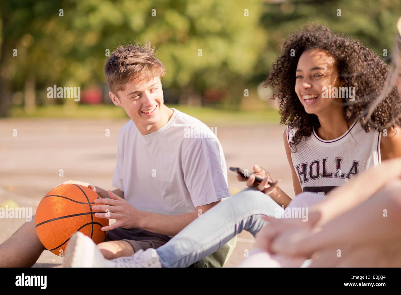 Group of young adult basketball players sitting chatting - Stock Image