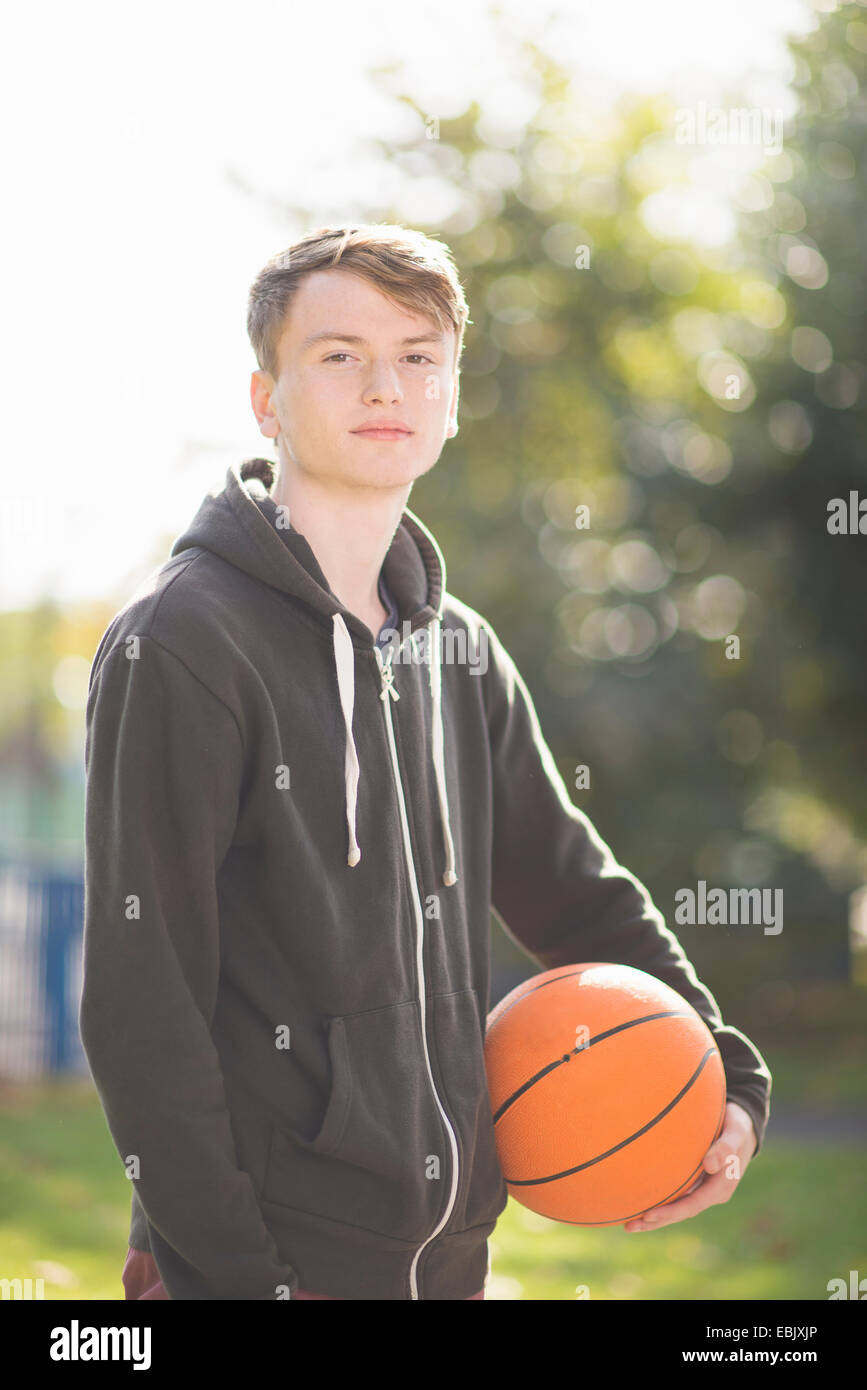 Portrait of young man holding basketball Stock Photo