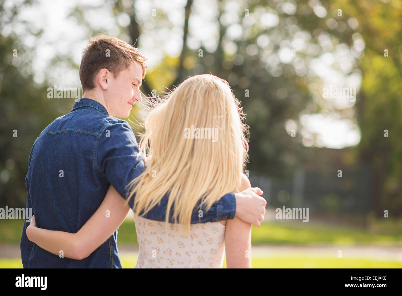 Rear view of romantic young couple strolling in park - Stock Image