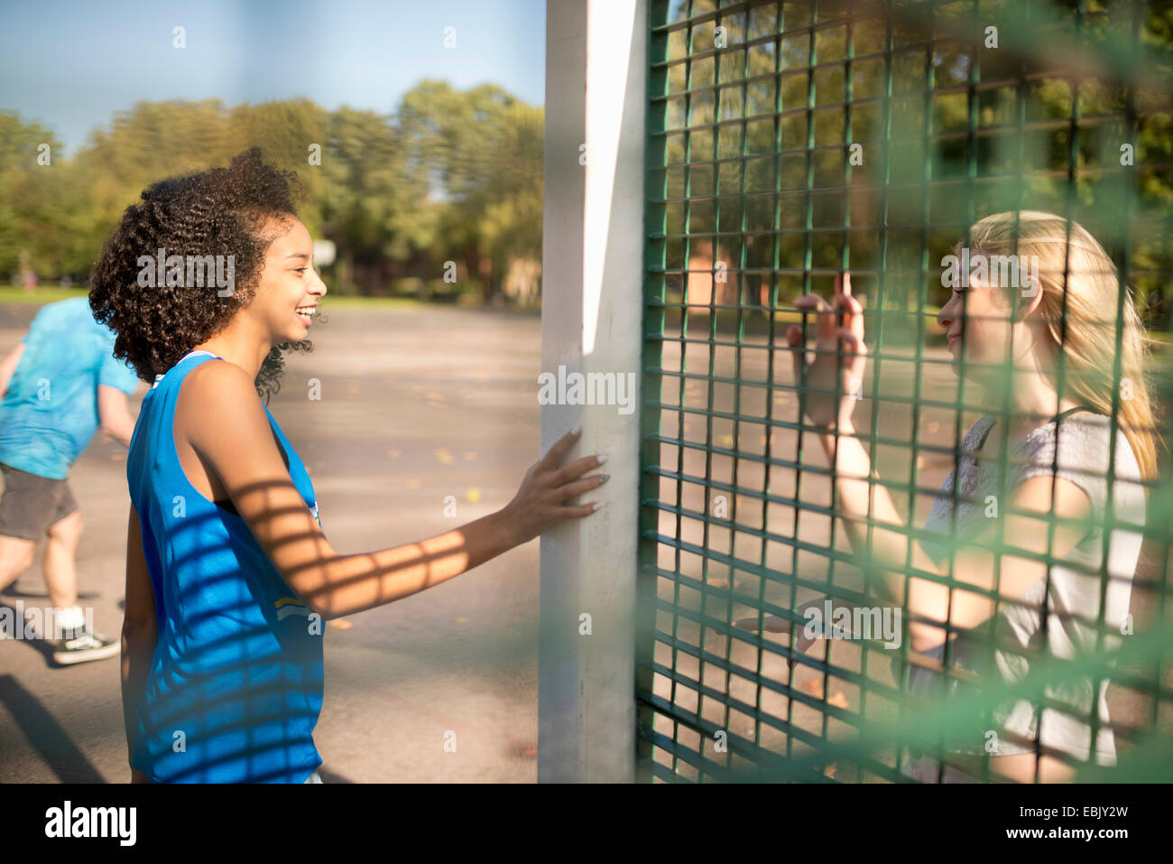 Two young female basketball players chatting on opposite wire fence - Stock Image