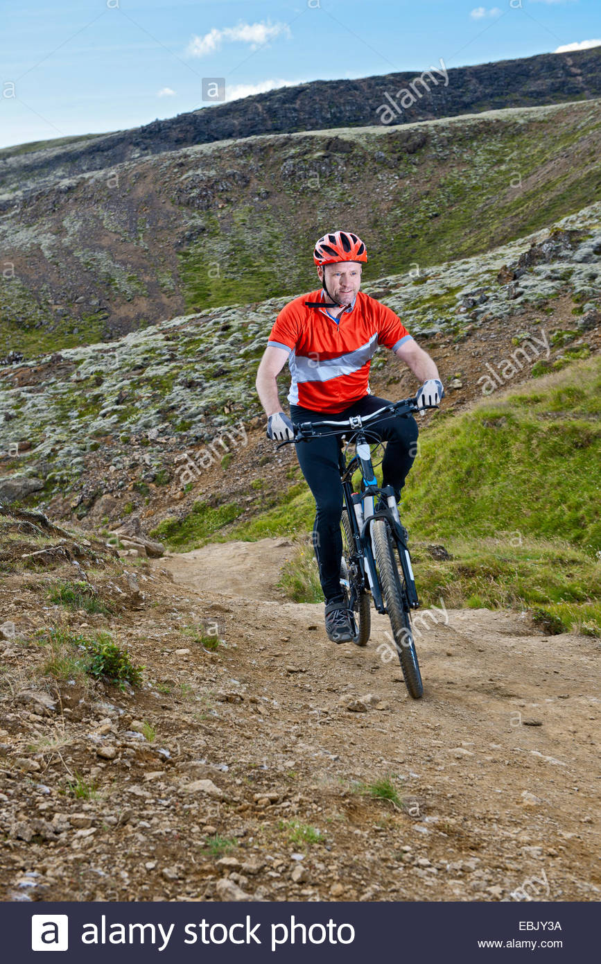 Male mountain biker cycling on dirt track, Reykjadalur valley, South West Iceland - Stock Image
