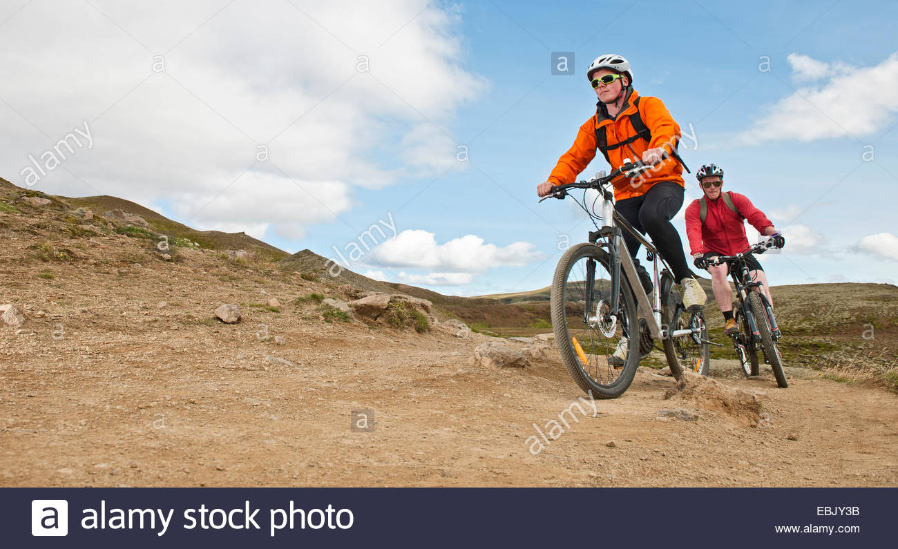Two young male mountain bikers cycling up dirt track, Reykjadalur valley, South West Iceland - Stock Image