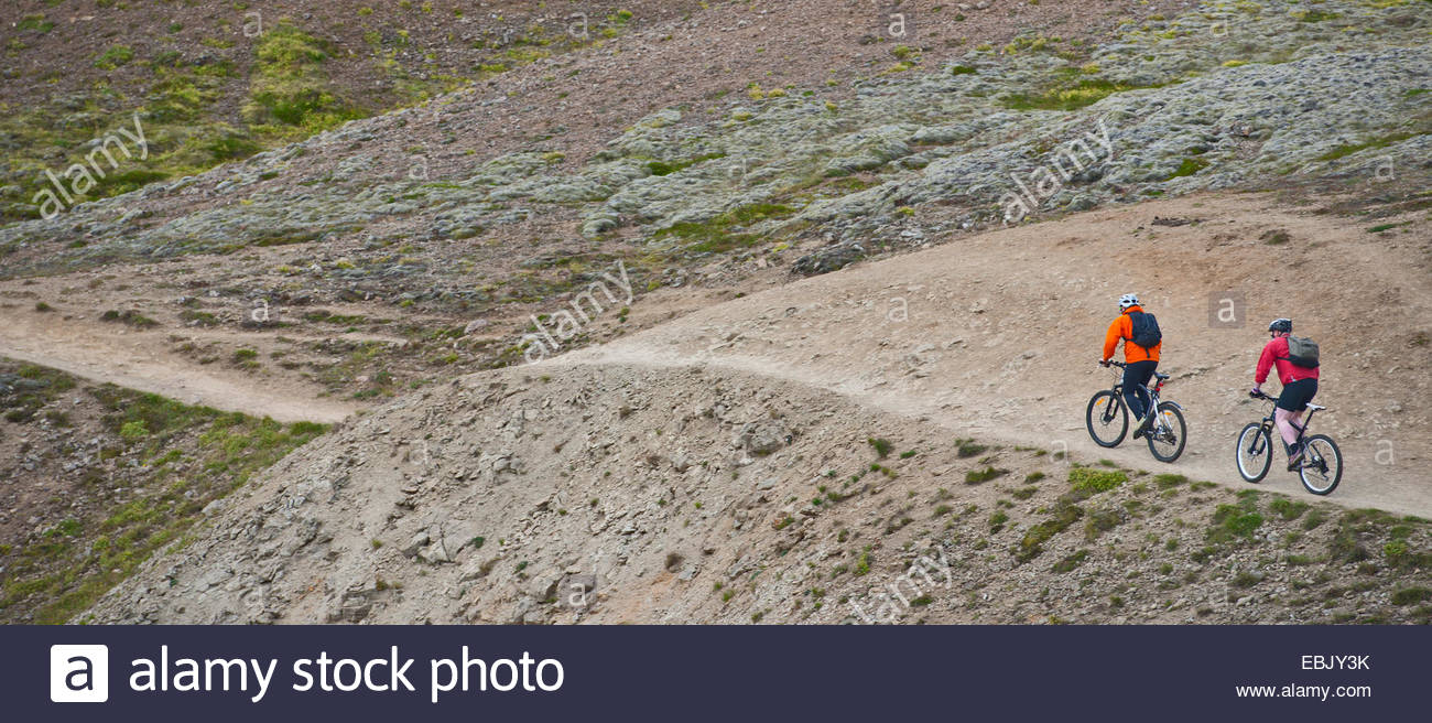 Two male mountain bikers cycling up dirt track, Reykjadalur valley, South West Iceland - Stock Image