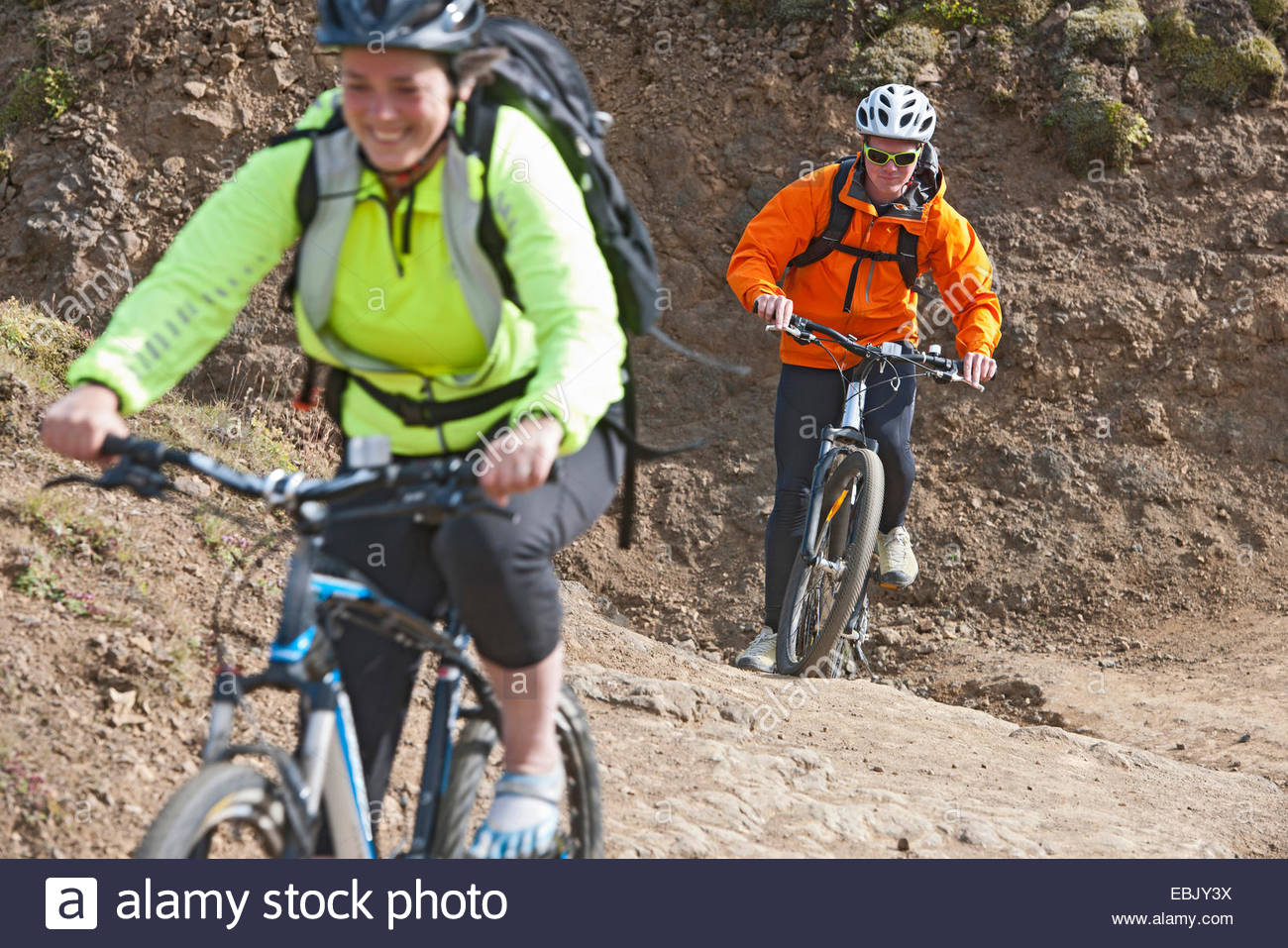 Close up of mountain bikers cycling on dirt track, Reykjadalur valley, South West Iceland - Stock Image