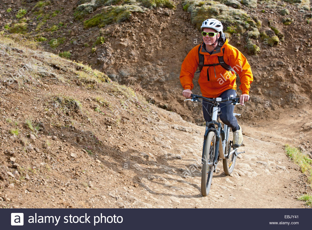 Young male mountain biker cycling up dirt track, Reykjadalur valley, South West Iceland - Stock Image
