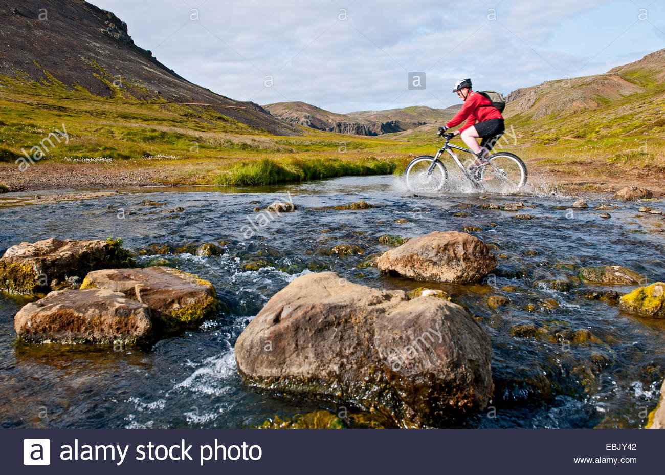 Young male mountain biker cycling through hot river, Reykjadalur valley, South West Iceland - Stock Image