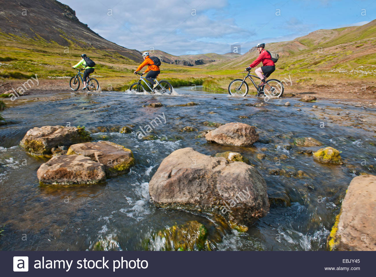 Mountain bikers cycling through hot river, Reykjadalur valley, South West Iceland - Stock Image
