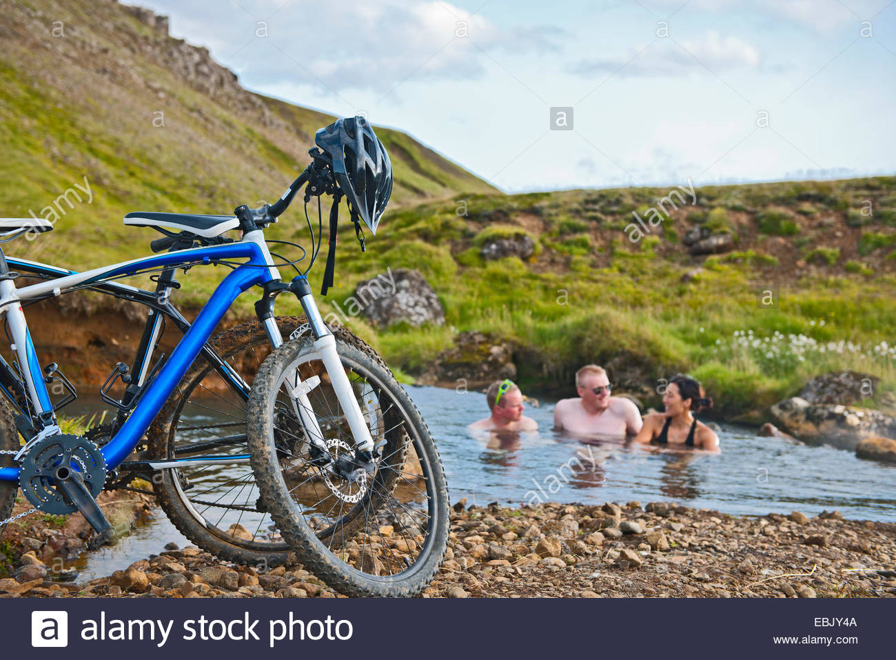 Three mountain bikers bathing in hot river, Reykjadalur valley, South West Iceland - Stock Image