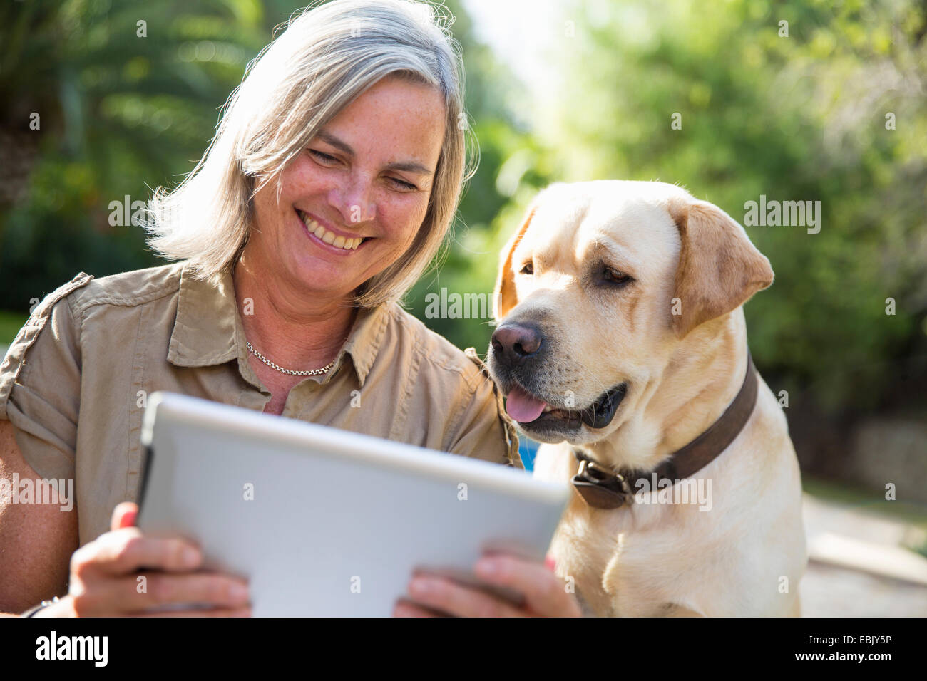Woman and dog looking at digital tablet - Stock Image