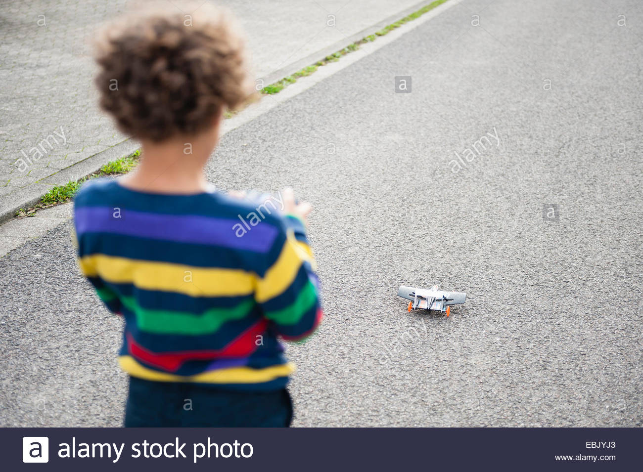 Rear view of boy playing on road with radio controlled airplane - Stock Image