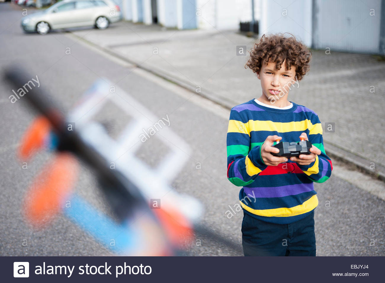 Boy playing with flying with radio controlled airplane - Stock Image